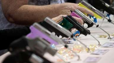 Attendees look over a pistol display at the