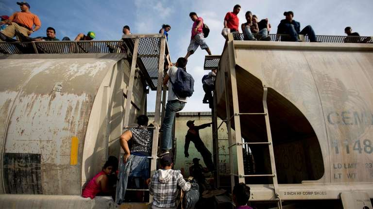 Central American migrants climb on a northbound train