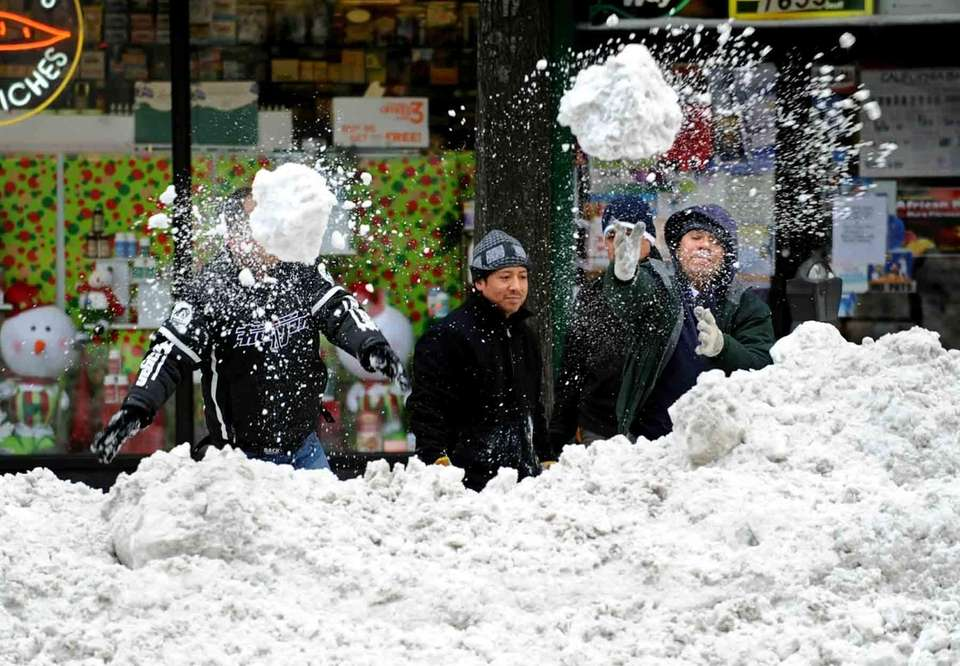 Men try to clear a pile of snow