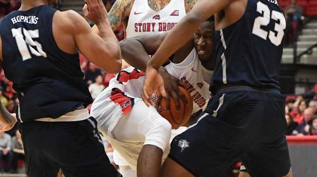 Stony Brook guard Elijah Olaniyi is defended by