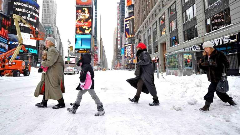 Tourists walk thorugh a nearly empty Times Square