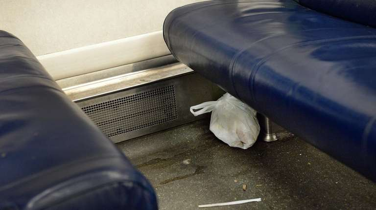 Trash is visible on a rush-hour LIRR train