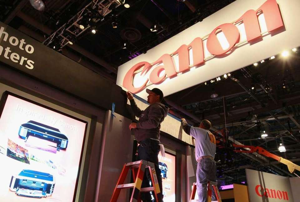 Workers apply vinyl letters at the Canon booth