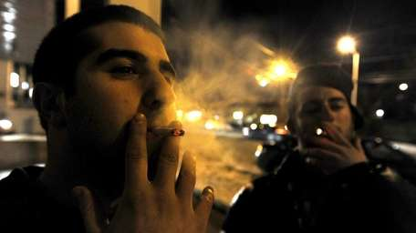 Smokers puff away in defiance of the new