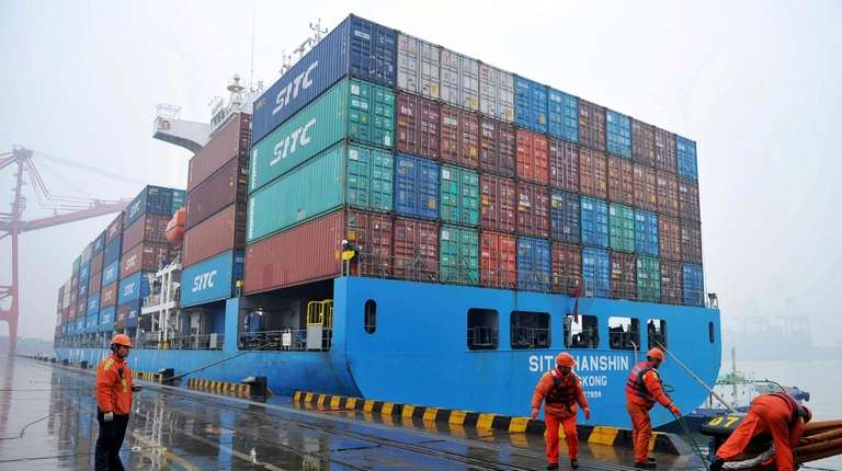 Workers moor a container ship at a port