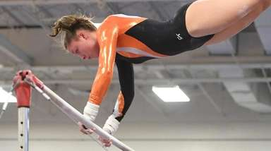 Hicksville's Kayla Corbett competes on the uneven bars