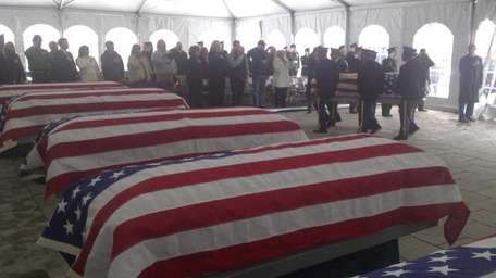 Flags are draped over the coffins of indigent