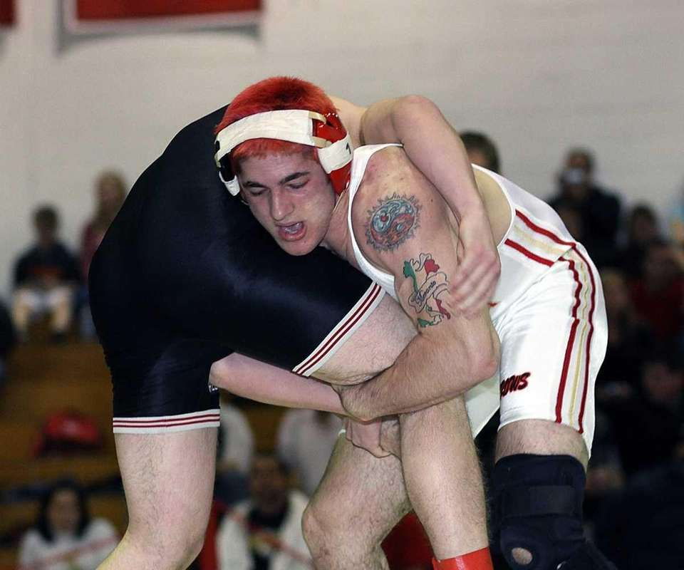 Sachem East's Frank Merante grabs the leg of