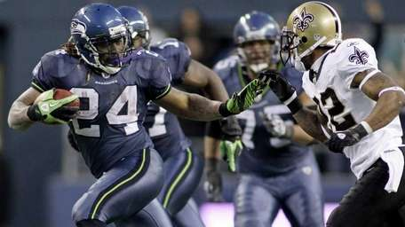 Seattle's Marshawn Lynch (24) breaks a tackle from