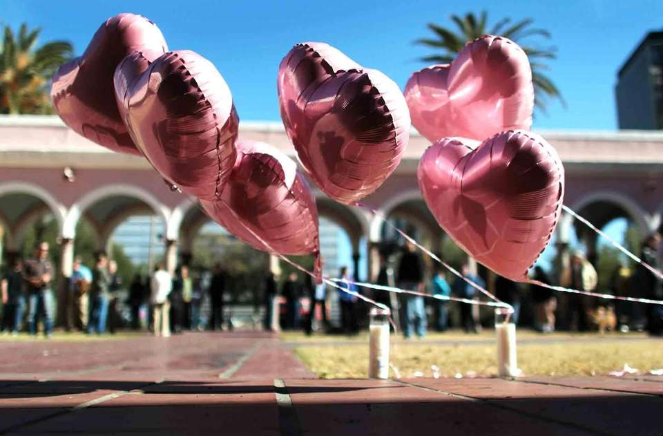 Six balloons fly at a prayer service, representing