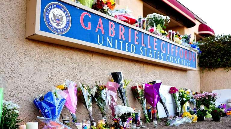 Flowers and candles are seen placed outside the