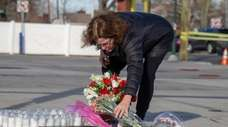 A woman leaves flowers at a makeshift memorial