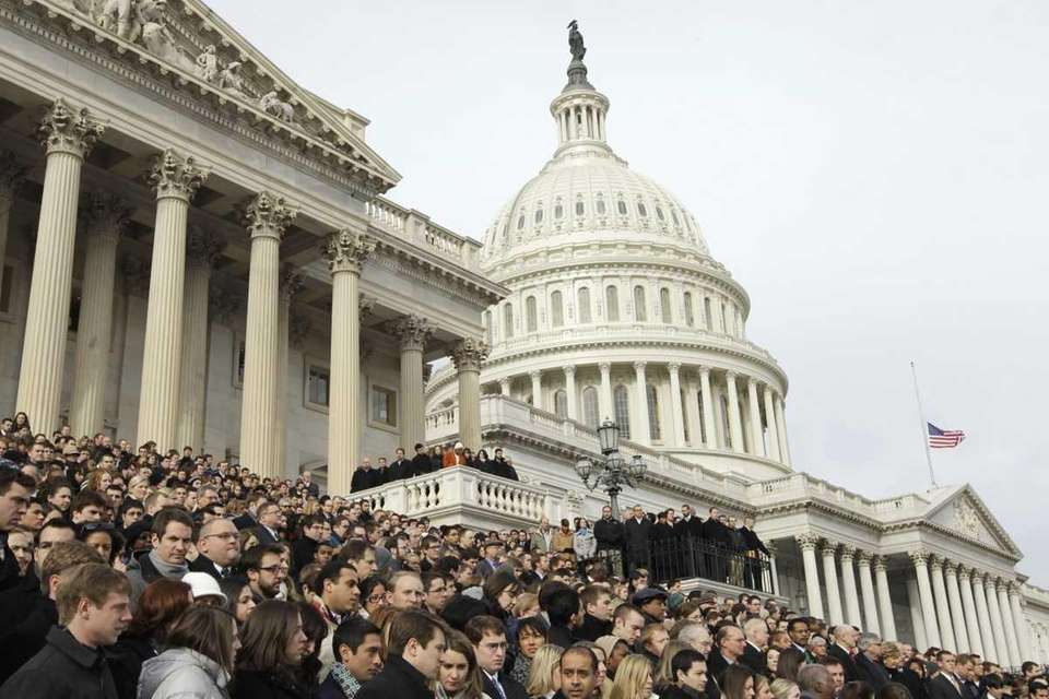 Members of Congress and staff members gather to