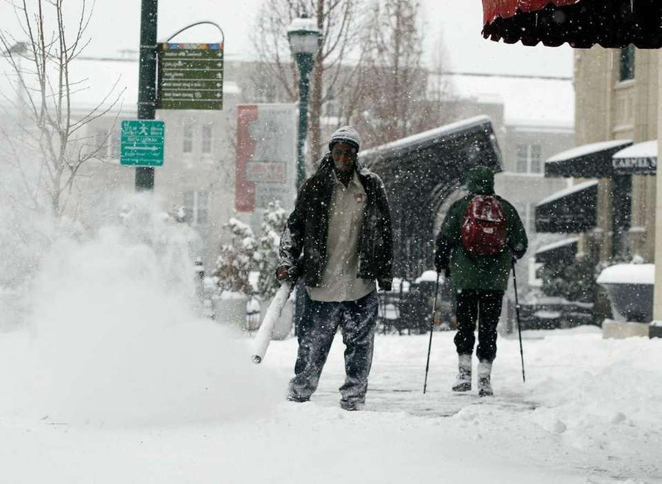 A hotel employee clears snow in downtown Asheville,