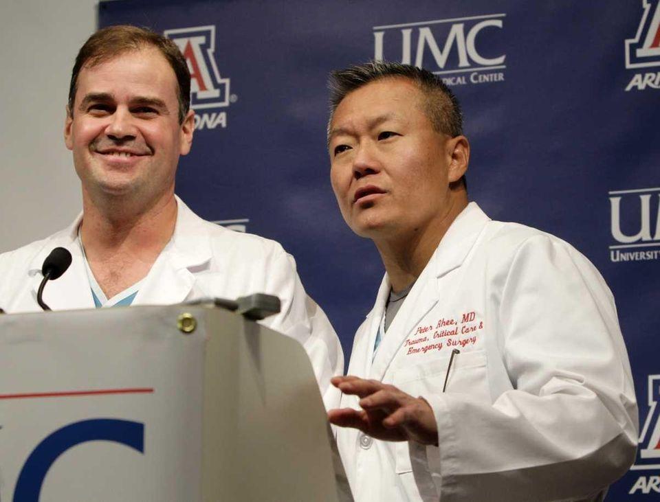 Dr. G. Michael Lemole, Jr., left, looks on
