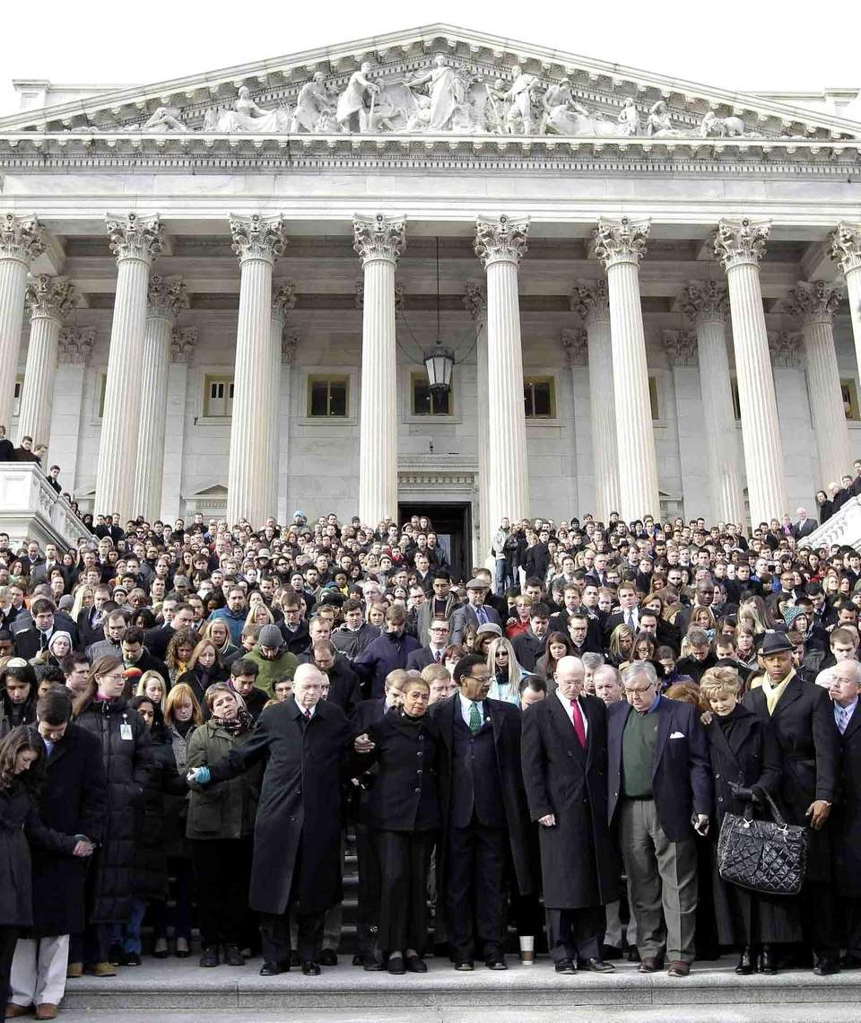 Members of Congress and staff observe a moment