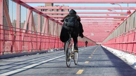A woman bikes across the Williamsburg Bridge into