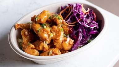 "Crisp, honey-glazed ""popcorn"" chicken with cole slaw is"