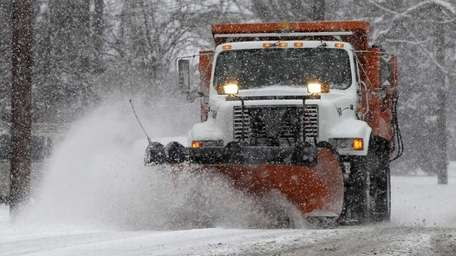 A snow plow moves down a street in