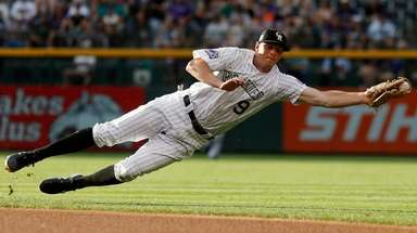 Then-Rockies second baseman DJ LeMahieu dives to field