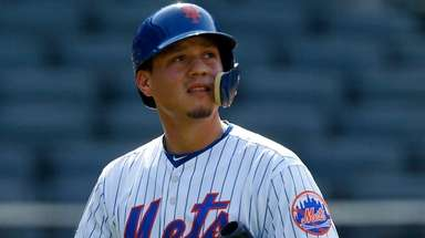 Wilmer Flores of the Mets strikes out against