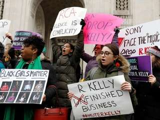 Demonstrators chant during an R. Kelly protest outside