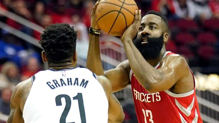 The Rockets' James Harden shoots as the Nets'