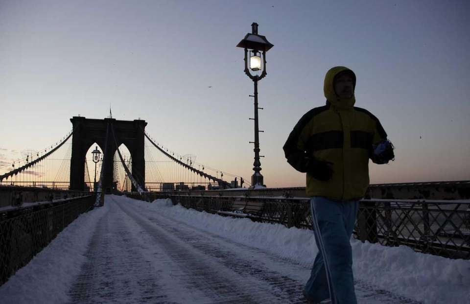 A jogger crosses the Brooklyn Bridge after a