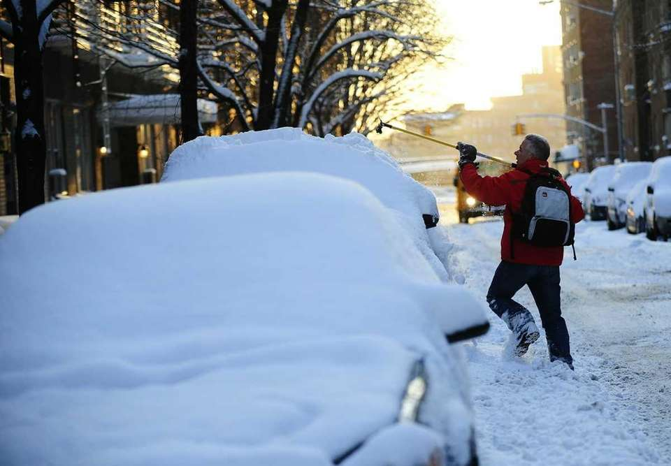 A man clears snow from his car as