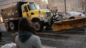 A woman watches a snowplow scrape Court Street