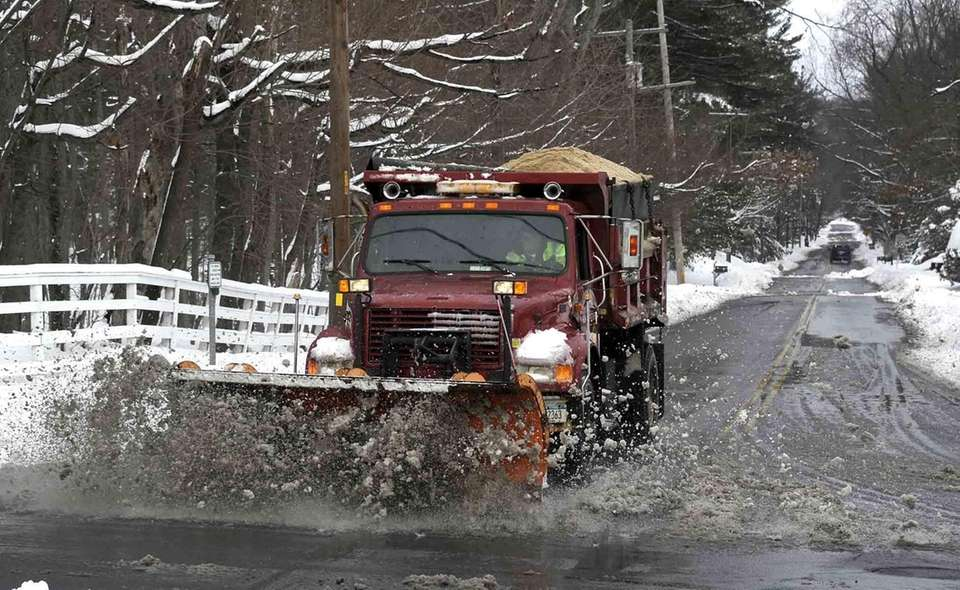 A snow plow clears slush and snow near