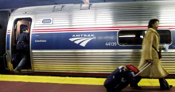 Passengers board an Amtrak train in Penn Station
