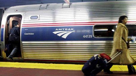 Passengers board an Amtrak train in Penn Station