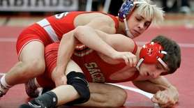 Connetquot's Christian Paredes, top, wrestles Sachem East's Lucas