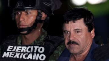 "Joaquín ""El Chapo"" Guzmán, right, is escorted by"