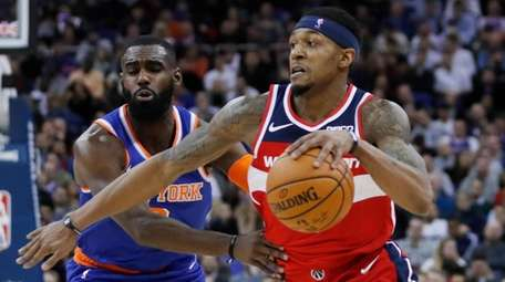 Wizards guard Bradley Beal, right, drives to the