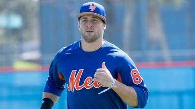 Mets outfielder Tim Tebow warms up during a