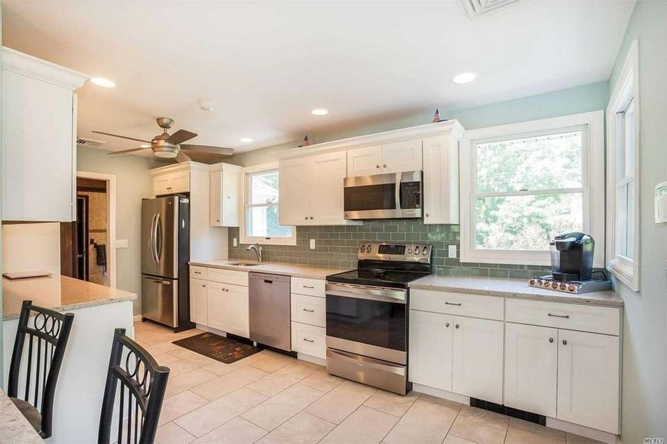 The updated kitchen features granite countertops and stainless