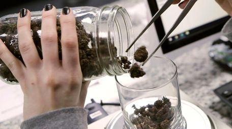 An attendant weighs marijuana at the Far West