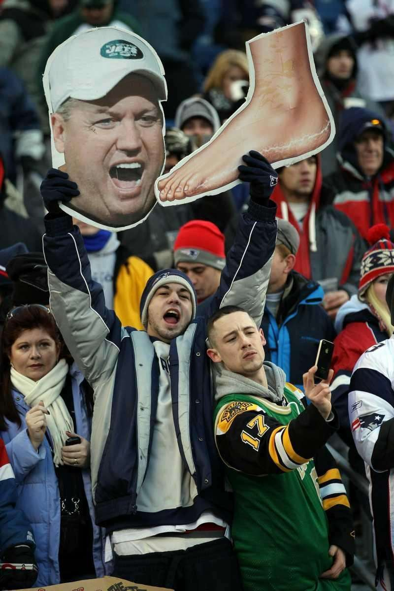 New England Patriots fans hold up signs picturing