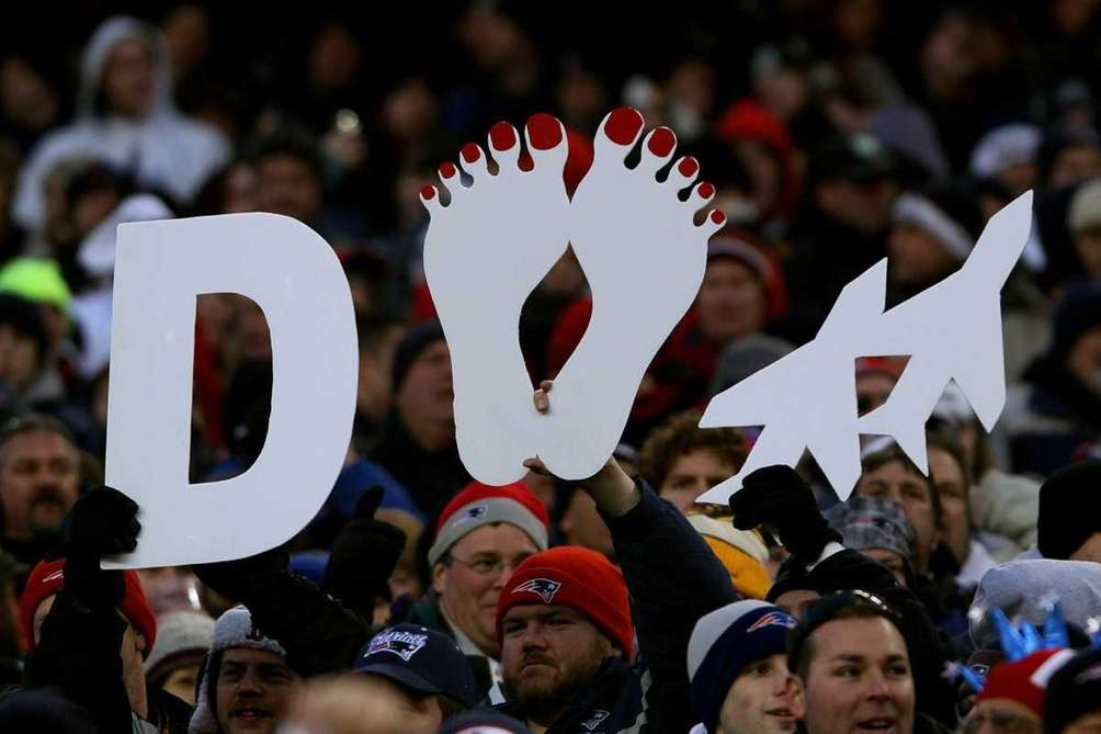 New England Patriots fans hold up a signs