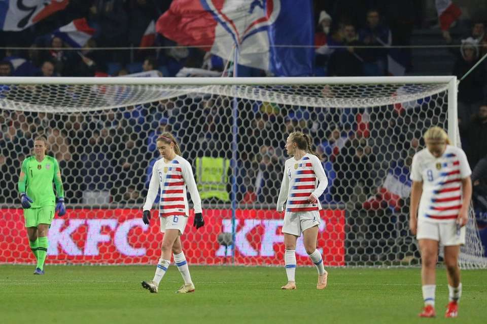 U.S. players walk along the pitch after France