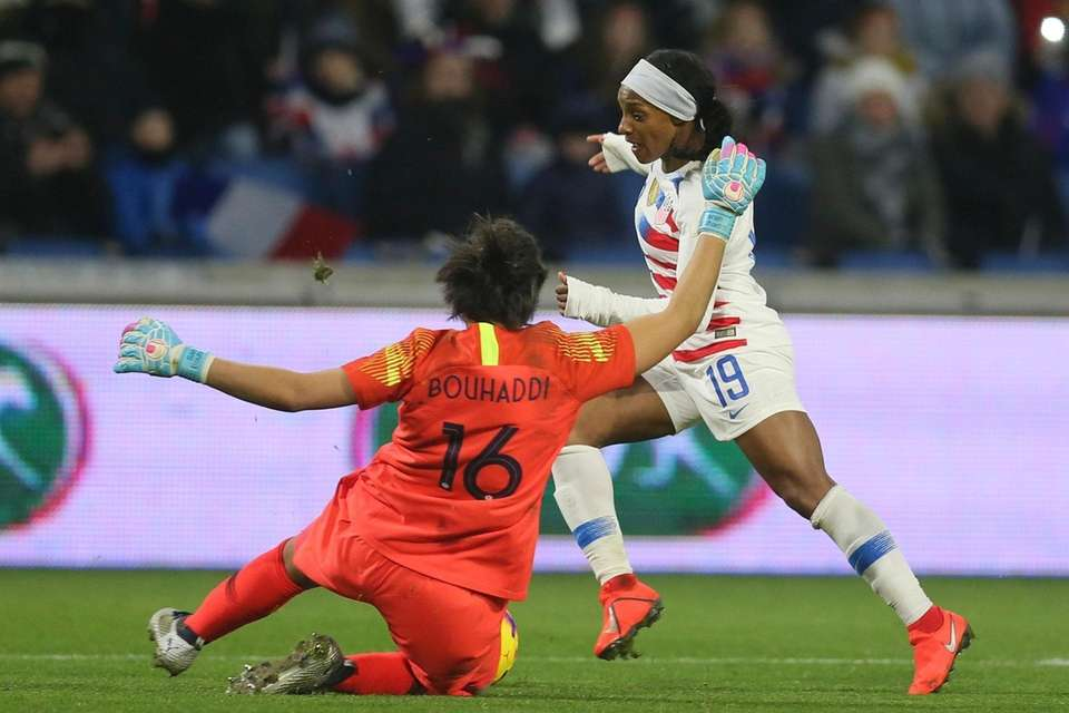 U.S. defender Crystal Dunn, right, challenges France goalkeeper
