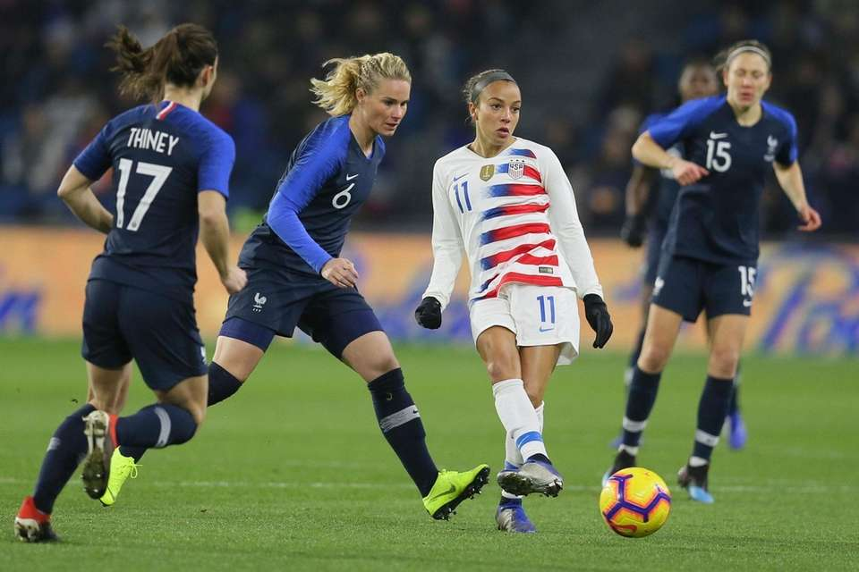 U.S. forward Mallory Pugh, right, shoots the ball