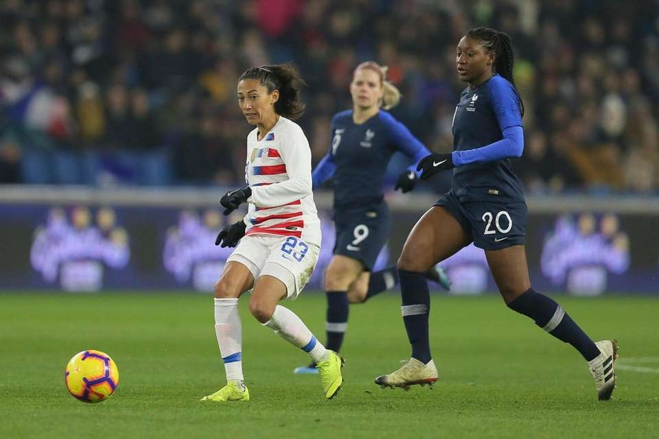 U.S. forward Christen Press, left, runs with the