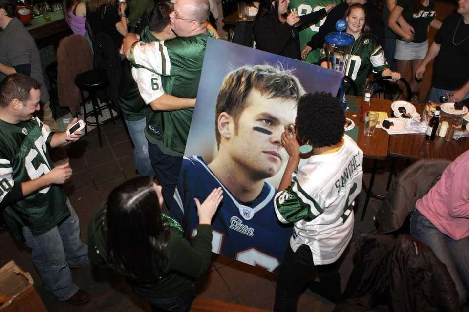 Jets fans pass around a poster-sized photo of