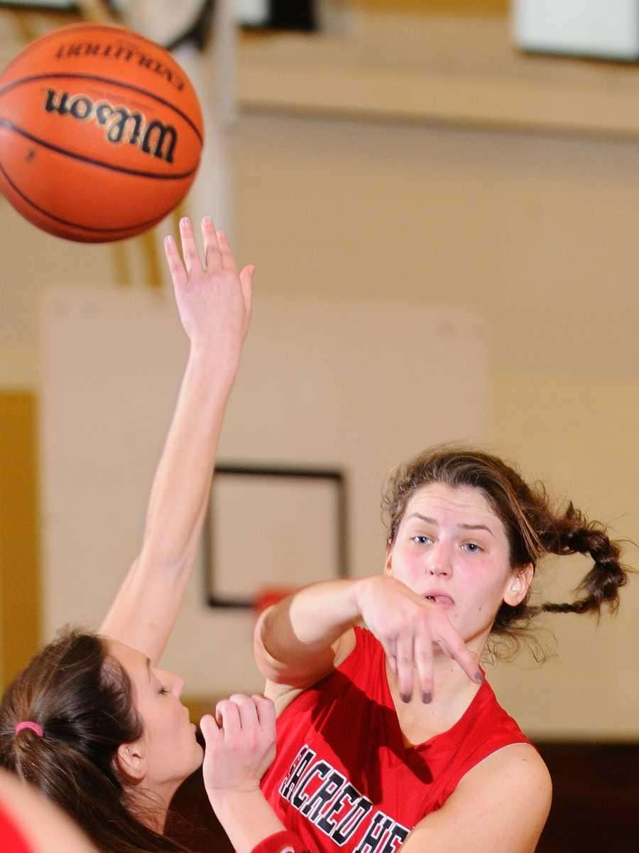 Sacred Heart's Taylor Higgins, right, dishes off a