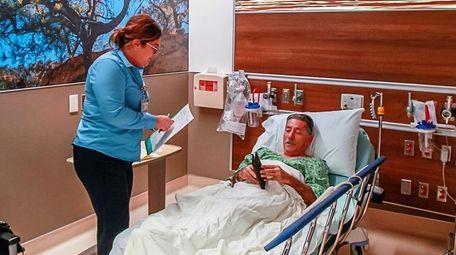 Patient access lead Alexis Hernandez, left, collects information