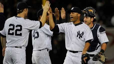 Yankees pitcher Mariano Rivera and teammates celebrate a