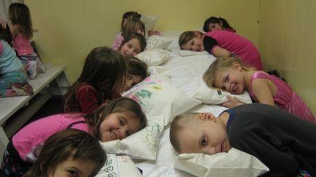 Kids show off their pillow artwork at a